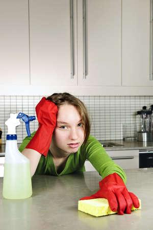 Chica cansada haciendo cocina, limpieza de las tareas domésticas con guantes de goma  Foto de archivo