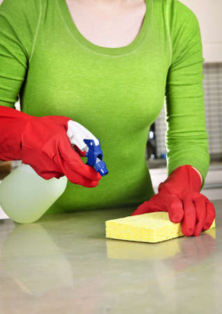 disinfecting: Girl cleaning kitchen  with sponge and rubber gloves