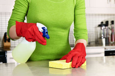 domestic kitchen: Girl cleaning kitchen  with sponge and rubber gloves