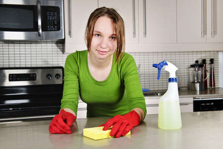 disinfecting: Young woman doing kitchen cleaning chores with rubber gloves Stock Photo