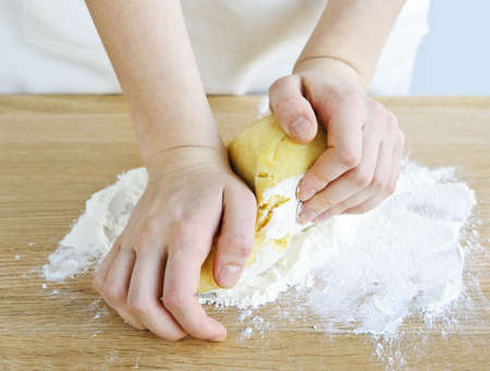 Hands kneading ball of dough with flour on cutting board photo