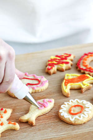 decorating: Decorating homemade shortbread cookies with icing from piping bag