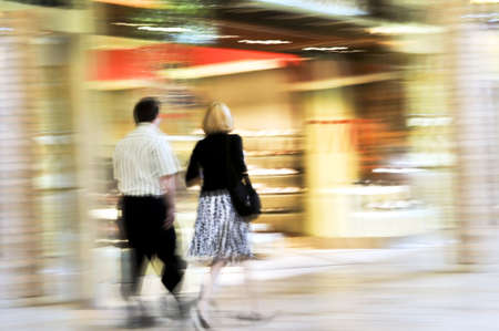 shop window: Couple shopping in a mall, panning shot, intentional in-camera motion blur