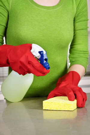 rubber: Girl cleaning kitchen  with sponge and rubber gloves