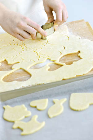 cutter: Woman using cookie cutter and baking homemade cookies