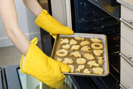 Taking fresh baked shortbread cookies from oven in kitchen photo