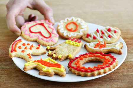 Hand taking cookie from plate of homemade shortbread cookies with icing photo