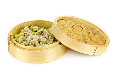 Bamboo steamer with cooked dumplings isolated on white Stock Photo