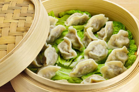 Closeup of bamboo steamer with cooked dumplings photo