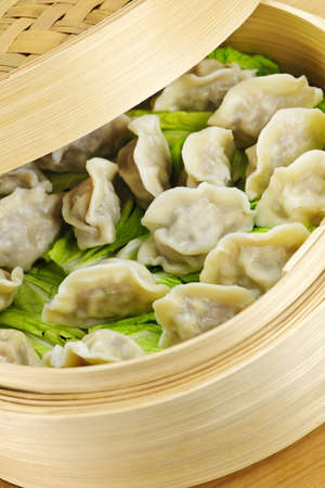 Closeup of bamboo steamer with cooked dumplings