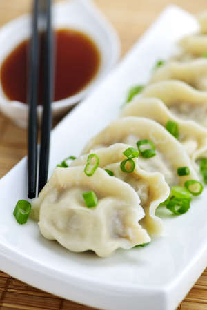 Plate of steamed dumplings with soy sauce and chopsticks