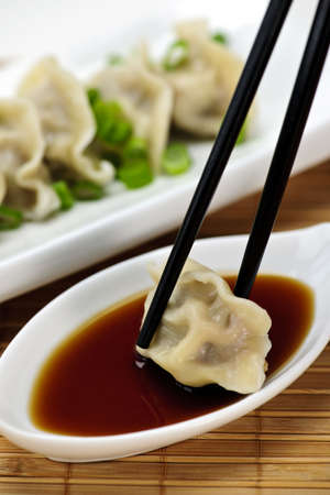 Dumpling being dipped in soy sauce with chopsticks
