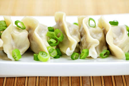 Plate of cooked chinese dumplings in a row