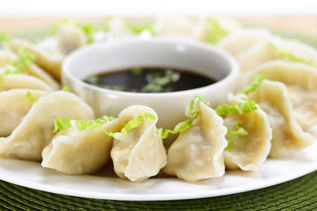 steamed: Closeup on plate of steamed dumplings with soy sauce