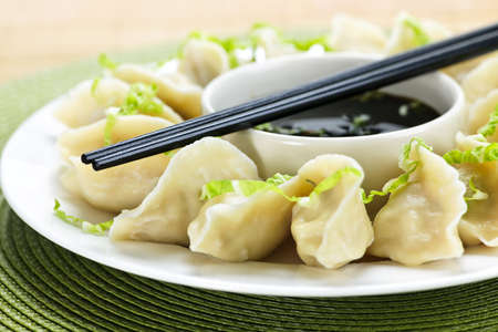 Closeup on plate of steamed dumplings with soy sauce and chopsticks Stock Photo