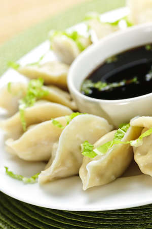 Closeup on plate of steamed dumplings with soy sauce