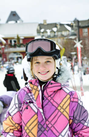 Portrait of happy teenage girl in ski helmet and goggles at winter resort photo