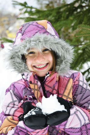 cold: Portrait of happy teenage girl holding snow in gloves Stock Photo
