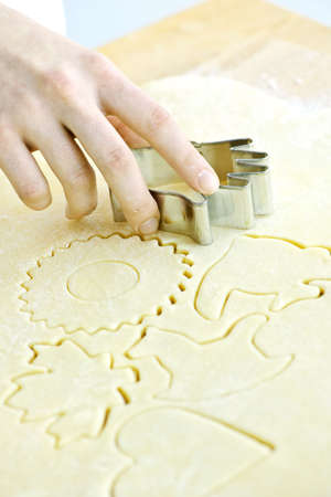 Cutting cookie shapes in rolled dough with cutter photo