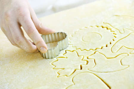 cutter: Cutting cookie shapes in rolled dough with cutter Stock Photo