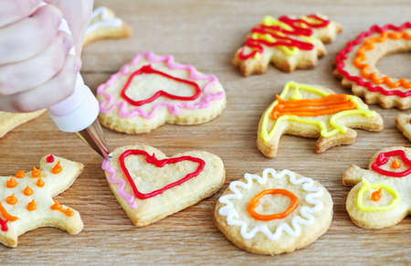 Decorating homemade shortbread cookies with icing from piping bag photo