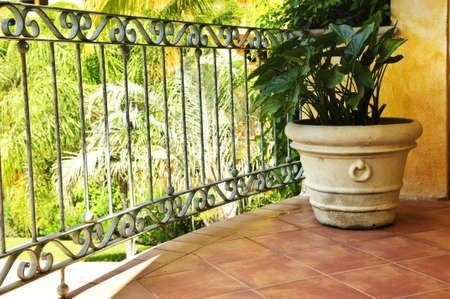 balcony: Tiled Mexican balcony with potted plant near railing Stock Photo