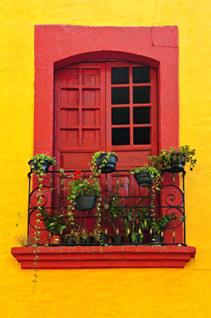 Red painted window with plants and wrought iron railing in Mexico