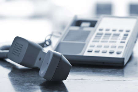 receiver: Telephone handset off the hook on desk Stock Photo