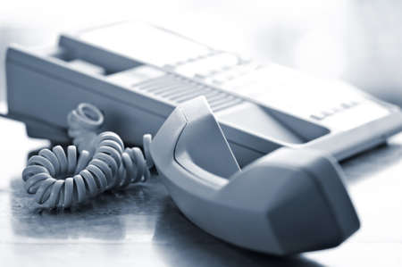 emergency call: Telephone handset off the hook on desk Stock Photo