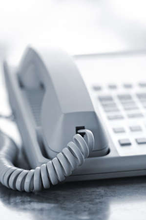 corded: Desktop telephone closeup hung up with cord