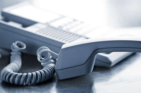 handset: Telephone handset off the hook on desk Stock Photo