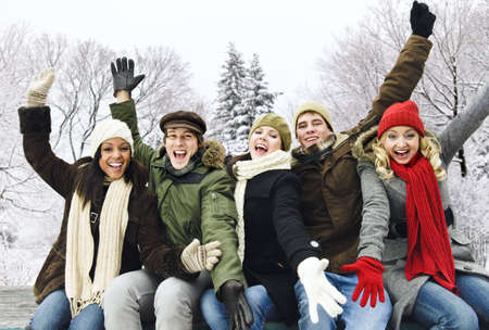 winter woman: Group of excited young friends with arms raised outdoors in winter