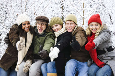 Group of diverse young friends showing thumbs up outdoors in winter photo