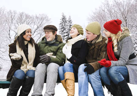 Group of young friends talking and laughing outdoors in winter photo