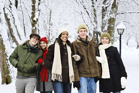 Group of diverse young friends walking outdoors in winter park photo