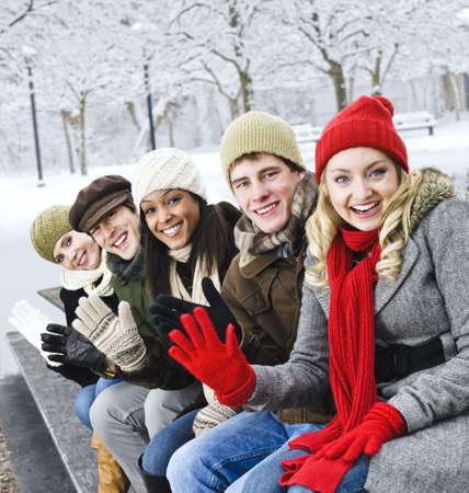 Groep van verschillende jonge vrienden hello buitenshuis te zwaaien in de winter