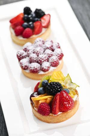 flan: Closeup of fancy gourmet fresh fruit dessert tarts