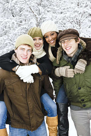 Group of young friends giving piggy back rides outdoors in winter photo