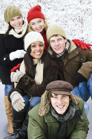 Group of young friends having fun outdoors in winter photo