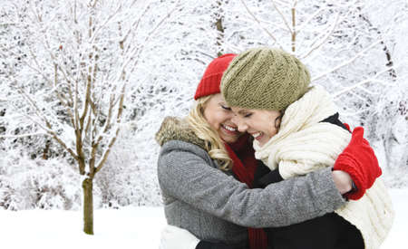Portrait of two young girl friends hugging outdoors in winter Archivio Fotografico