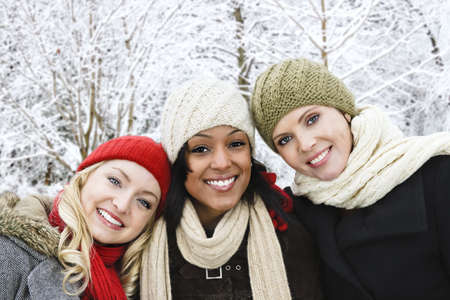 winter woman: Group of three diverse young girl friends outdoors in winter