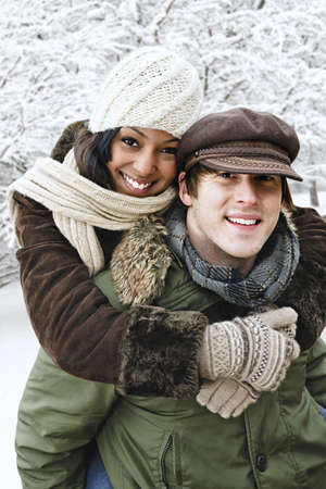 piggyback: Portrait of couple having piggyback ride outdoors in winter