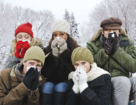 miserable: Group of diverse young friends blowing noses outdoors in winter