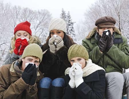 gripe: Grupo de amigos de j�venes diversas soplado narices al aire libre en invierno