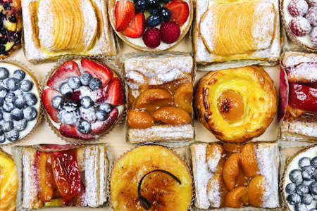 danish: Background of assorted fresh sweet tarts and pastries from above