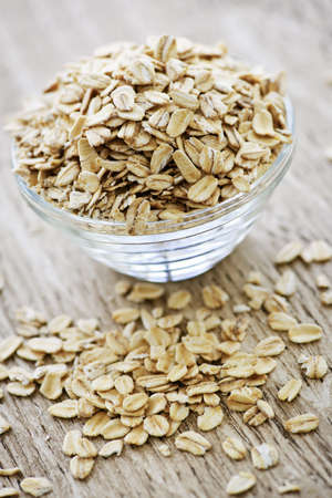 heaped: Nutritious rolled oats heaped in a glass bowl Stock Photo