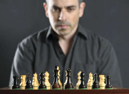 Man looking at wooden chess board thinking about first move photo