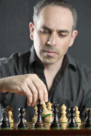 Man moving a chess pawn on wooden chessboard as first move Imagens