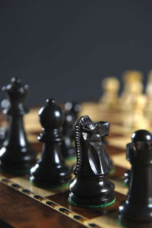Close up of black chess pieces on wooden chessboard photo