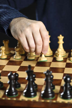 Hand moving a pawn chess piece on wooden chessboard as first move photo